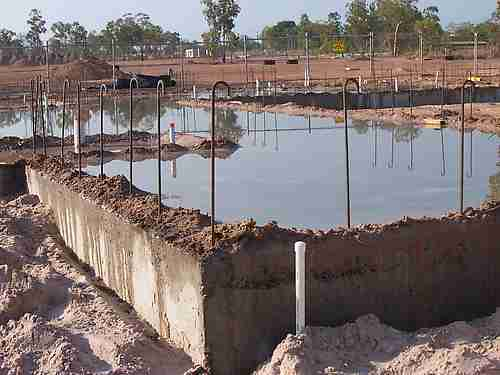 Curing a concrete house slab by flooding