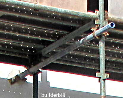 a putlog securing a section of scaffold to a wal