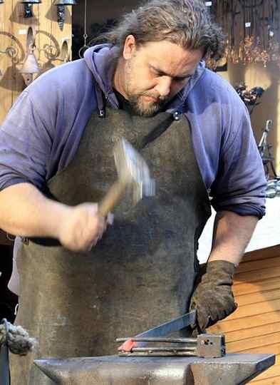 A smith usinng a straight Peen hammer